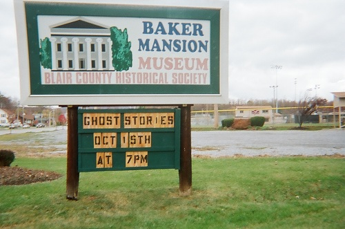 Pennsylvania tourist attractions green blue and tan Baker Mansion sign surrounded by green grass and Mansion Park in the background