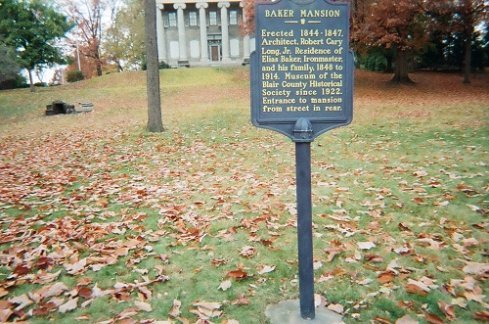 blue sign in the yard at Baker Mansion with fall leaves on the grass