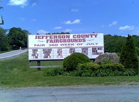 Jefferson County fair white and light maroon sign on green grass surrounded by green trees and green bushes with a blue sky and white clouds overhead