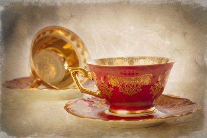 antique tea cups sitting on antique deep pink colored saucers