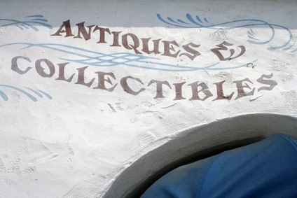 antiques and collectibles written in maroon letters on a vintage shop