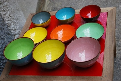 colored ceramic bowls for sale at a stand at a festival