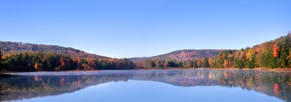 Chapman State Park in Pennsylvania with green, orange and gold colored tree leaves reflecting in the blue lake with baby blue sky above