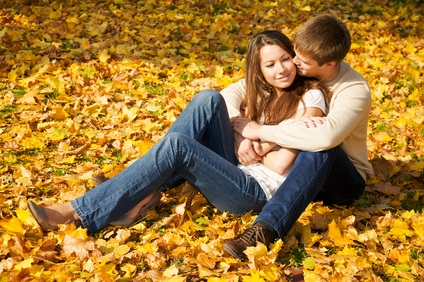couple sitting in a PA state park on a pile of yellow and green autumn leaves