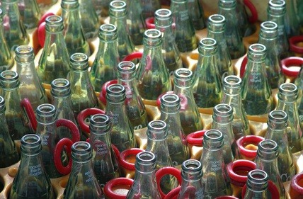 empty soda bottles in rows with red rings at a fair where people try to win prizes by getting a ring around the bottle neck