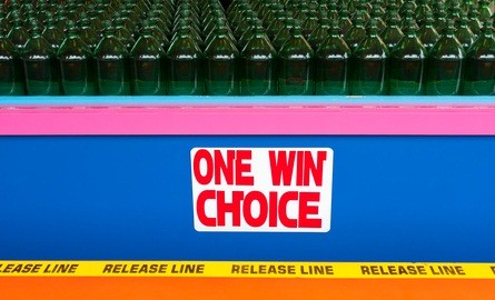 bottle toss on a pink and blue game board with one win choice written in red letters on the front