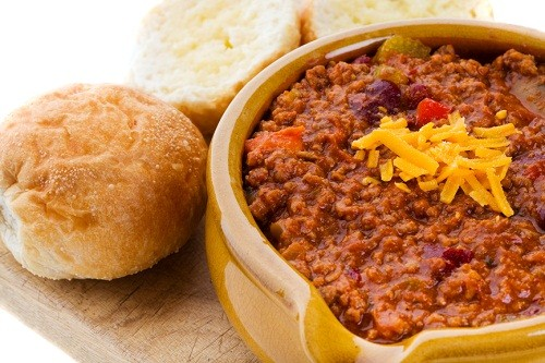 bowl of festival chili in a yellow bowl with two rolls
