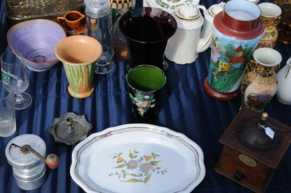 bowls, mugs, a wooden box and white plate on a blue cloth at a flea market