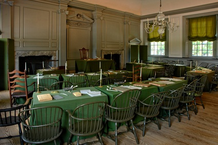 tables with green cloths and wire chairs in a room with a crystal chandelier, two fireplaces and windows with olive green curtains in Philadelphia Independence Hall