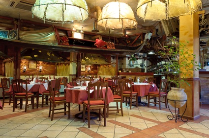 Italian restaurant with tables, a pillar and white overhead lights