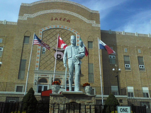 Jaffa Shrine building with a shriner statue holding a child and three flags, one the American flag with blue sky overhead