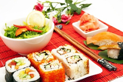 Japanese restaurant sushi on a red placemat with chopsticks and a white bowl with veggies