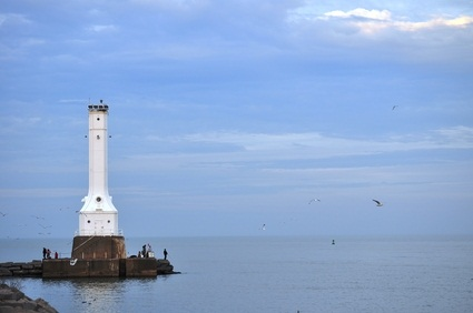 Lake Erie lighthouse on the blue water with seagulls flying under a blue sky
