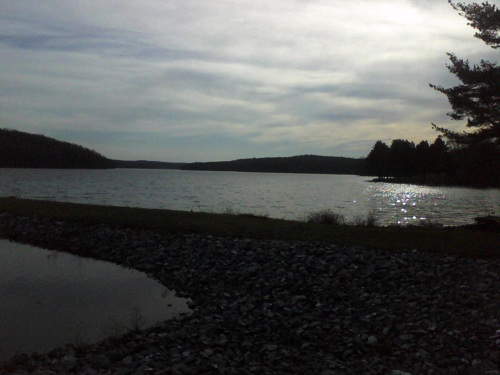state park lake as the sun is starting to leave the area with two separate parts of the lake water, stones, and mountains with white clouds