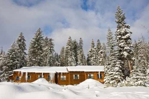 lodge in the winter with snow on the ground and pine trees