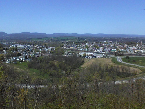 lower lookout at Chimney Rocks in Hollidaysburg overlooking the borough with buildings and houses, road, mountains, green fields and blue sky
