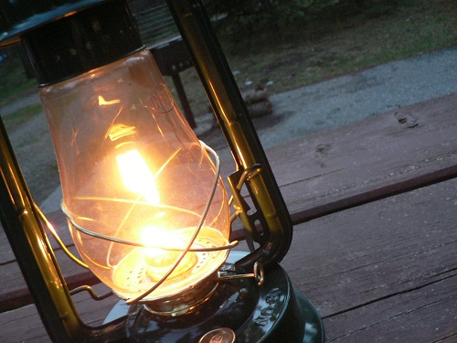 one lit lantern outside on a picnic bench