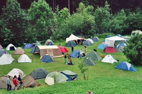 blue, white, gray and brown tents on the green grass surrounded by trees