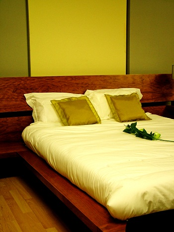 online vacation planning hotel room hotel bed with rose on bedspread