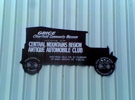 PA museums Grice Clearfield Community Museum classic car sign with white letters on the side of a bluish gray building in Clearfield County PA