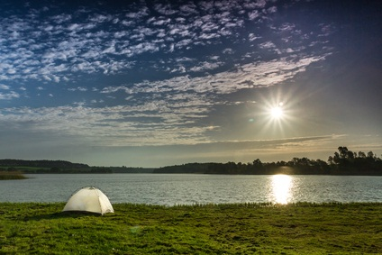 white tent on green grass overlooking a gray water lake as the sun shines in the gray sky and reflects off the water with mountains behind