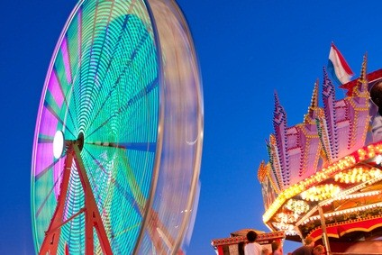 ferris wheel with pink, blue and green lights beside the top of a merry go round at the fair