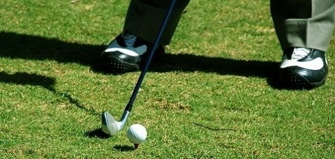 golfer on the greens with a club and ball on golf resort vacations