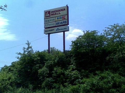 red and white Indiana Mall sign on a hilltop with green trees below and a blue sky with white clouds overhead