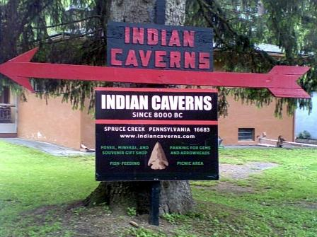 Pennsylvania tourist attractions Indian Caverns sign in Spruce Creek PA with red, white and green lettering hung on a tree with a big red arrow