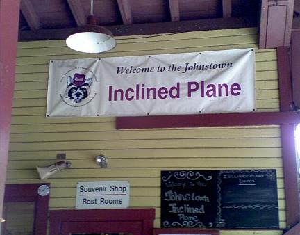 white and purple Johnstown PA inclined plane sign on tan outside walls surrounded by purple beams and poles