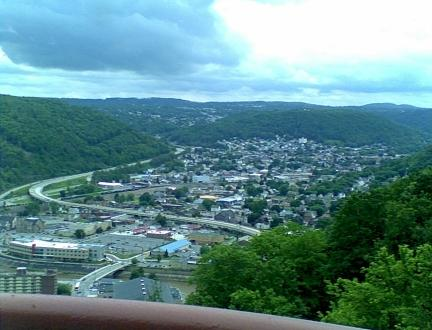 Johnstown PA inclined plane view from the top of the incline showing the city scape, green mountains, blue sky and white clouds