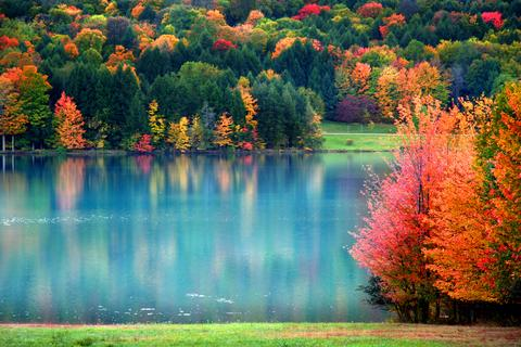 fall in PA pink, green yellow and orange colored tree leaves reflecting off the blue water lake