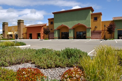 outlet center in Pennsylvania with shrubs and an empty parking lot with bright blue sky