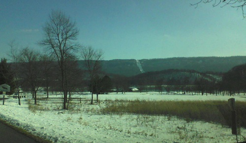 winter day in January at a Pennsylvania state park with snow on the grass and mountains in the backdrop underneath a blue sky