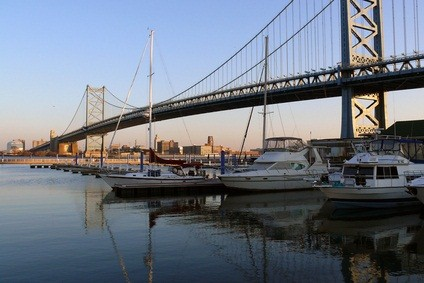 three boats on the blue water underneath the Ben Franklin Bridge in Philadelphia