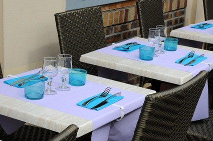 restaurant indoors with square white tables, chairs, blue napkins, glasses and silverware