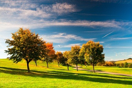 golf resort in the Poconos in PA with blue sky, white clouds, green grass and trees with orange, yellow and green leaves