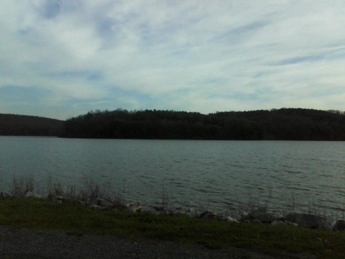 blue-gray lake water with a mountain backdrop and blue sky with white clouds in the Poconos on a late fall day