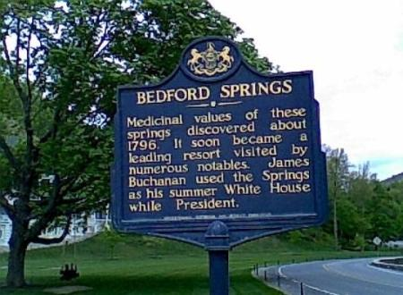 resorts in PA Bedford Springs Bedford PA blue sign surrounded by green grass and green trees