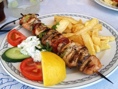 pork souvlaki in a Greek restaurant in Pennsylvania with a slice of cucumber, tomatoes, lemon slice and french fries on a white plate with blue trim