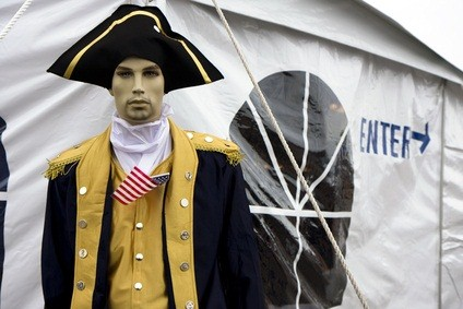 statue of a soldier in the Revolutionary War with a blue and gold jacket, American flag, and hat beside a white tent with Enter written in blue letters