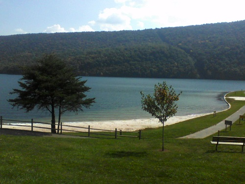 pennsylvania forums blue river with a mountain backdrop, green grass, trees, a sand beach and bench