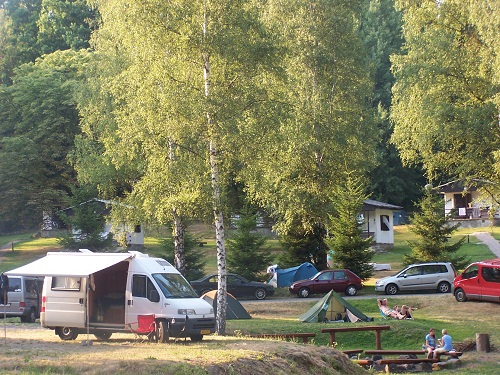 RVs, tents, cars, people at a campsite with wooden benches