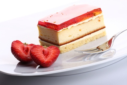 strawberry dessert on a white plate with sliced strawberries and a fork