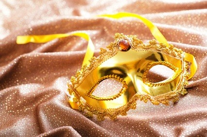 gold stage mask on a tan silk fabric