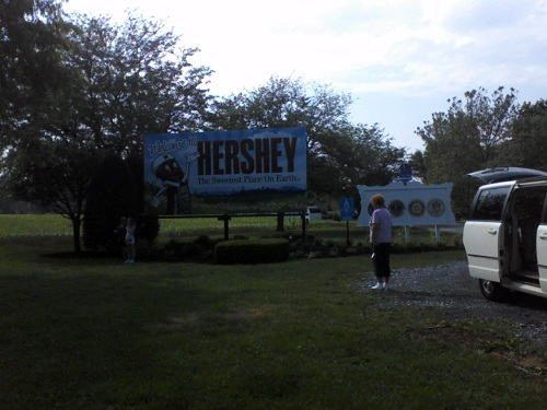 travel forum welcome to Hershey white and brown sign with a chocolate bar on it on green grass in Hershey PA, Dauphin County PA