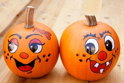 two pumpkins at the festival with happy painted faces