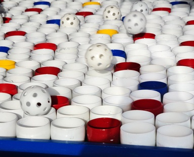red, blue, white and yellow cups at a fair with wiffle balls trying to land on a cup