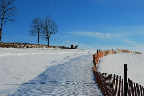 Pennsylvania Amish Country in the winter with snow and a horse and buggy with blue sky above