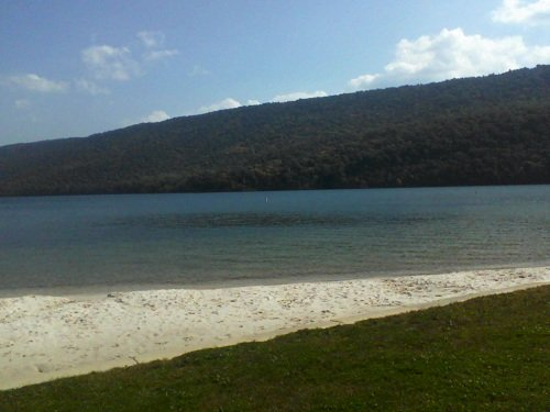 blue water of a PA river with a sand beach, green grass, mountains, blue sky and white clouds